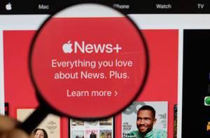 Logo und Schriftzug von Apple News+,  vergrößert durch eine Lupe dargestellt
