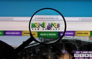 Logo vom Faschingsanlass Mardi Gras in New Orleans auf Computerbildschirm mit Lupe