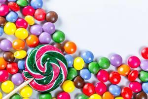 Lollipop liegt auf bunten Süßigkeiten in Kugelform auf weißem Hintergrund