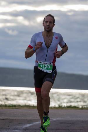 Long-distance runner during the Ironman 70.3 half marathon at the Finnish coast of Vesijärvi in Lahti