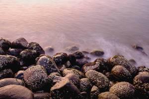 Long exposure of small waves hitting rocks