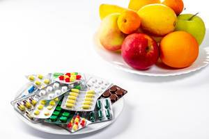Lots of colorful pills and fresh fruit on white background