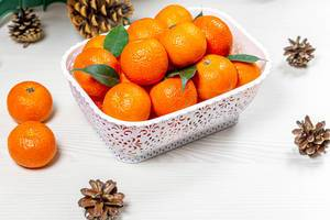 Lots of fresh tangerines on white wooden background with cones (Flip 2019)