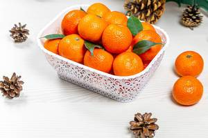 Lots of fresh tangerines on white wooden background with cones