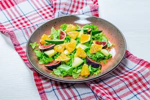 Low-calorie salad with fresh lettuce, oranges, figs and mango. The concept of vegetarianism, weight loss (Flip 2019)