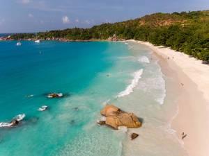 Luftaufnahme der Bucht Anse Lazio mit braunen Granitfelsen am weißen Sandstrand und türkis-blauem Wasser auf Praslin, Seychellen