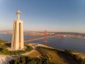 Luftaufnahme der Cristo Rei Statue und der Ponte 25 de Abril Brücke von der Seite in Almada Lissabon