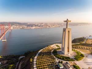 Luftaufnahme der Cristo Rei Statue von hinten mit Ponte 25 de abril Brücke in Almada Lissabon