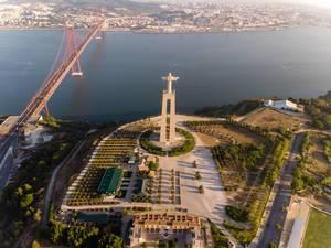 Luftaufnahme der Cristo Rei Statue von hinten mit Ponte 25 de abril Brücke