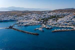 Luftaufnahme des Dorfs Naoussa auf der Kykladeninsel Paros, Griechenland, mit Hafen und alter Burgruine, in der Bucht Ormos Naousia