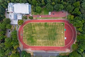 Luftaufnahme eines Sportplatz mit Laufbahn und Wiese, neben der Trainingshalle des ASV Köln, umgeben von Wald