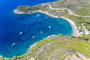 Luftaufnahme mit Blick von der steilen Küste, zu teuren Jachten in der Meeresbucht am Plaza Paraskevi Strand