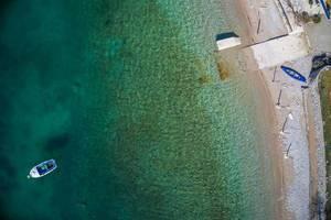 Luftaufnahme mit der Drohne von einem Kiesstrand und türkisblauem Wasser