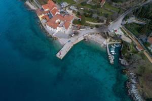 Luftaufnahme mit der Drohne von einer kleinen Bucht mit Bootssteg und Kloster an einem Kiesstrand
