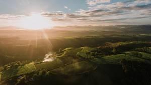 Luftaufnahme Sonnenstrahlen treffen auf Felder und Natur in Don Salvador, Negros, Philippinen
