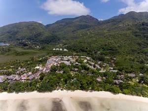 Luftaufnahme vom Constance Ephelia Resort vor den grünen Hügeln des Morne Nationalpark auf den Seychellen mit Port Launay Strand
