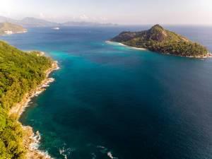 Luftaufnahme von der Seychelleninsel Therese umgeben vom blauen Ozean, aus Richtung Anse des Anglais im Constance Ephelia Resort, Mahé