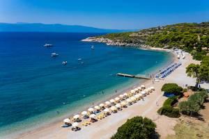 Luftaufnahme von gelben und blauen Liegestühlen in einer Reihe, unter Sonnenschirmen, an einem Strand in Agii Anargiri, am Myrtoischen Meer