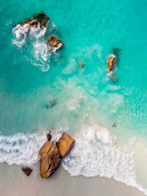Luftaufnahme von Granitfelsen im grünen Meer und seichten Wellen am Strand von Anse Lazio auf Praslin, Seychellen