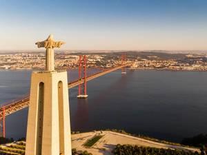 Luftaufnahme von hinten der Cristo Rei Statue und ponte 25 de abril Brücke in Almada Lissabon