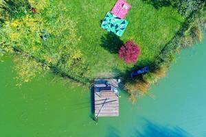 Luftaufnahme von Holzsteg mit Angelzubehör und Wiese mit Picnickdecken