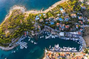 Luftaufnahme von mediterranen Villen und Schiffen im Hafen der Saronische Insel Spetses in Griechenland