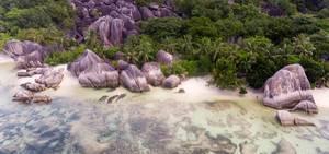 Luftaufnahme von mehrfarbigen Granitfelsen zwischen Tropenbäumen und Palmen am Anse Union-Strand auf La Digue, Seychellen