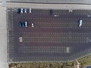 Luftaufnahme von riesiger Parkfläche mit nur wenigen geparkten Fahrzeugen