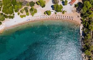 Luftaufnahme von Touristen im Urlaub und schwimmen im grünen Meer am Plaza Paraskevi-Strand in Agii Anargiri, Spetses