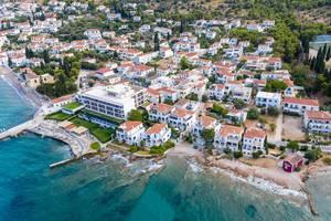 Luftaufnahme zeigt aristokratische Villen, neben dem Spetses Hotel mit Privatstrand, am türkisen Meer