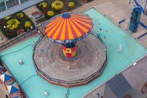 Luftaufnahme zeigt ein fahrendes, leeres Kettenkarussell in Zirkuszeltfarben