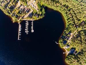Luftaufnahme zeigt Jachten und Motorboote an Holzstegen auf dem Päijännesee bei Padasjoki geparkt, neben luxuriösen Ferienhäuser