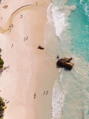 Luftaufnahme zeigt Seychellen-Urlauber auf dem weißen Sandstrand Anse Lazio auf Praslin mit Granitfelsen und Wellen des Indischen Ozeans