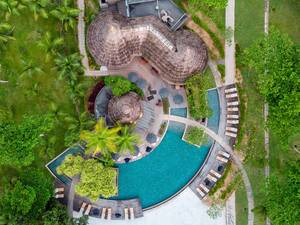Luftaufnahme zeigt Terrassendeck und Cafés mit Bastdach an rundem Pool im Constance Ephelia Luxusresort auf Mahé, Seychellen