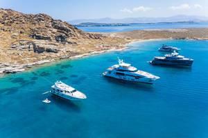 Luftaufnahme zeigt Urlauber in den Sommerferien auf dem blauen Mittelmeer, mit teuren Yachten vor der Küste der griechischen Insel Paros