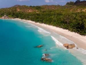 Luftaufnahme zeigt Urlauber in der Bucht Anse Lazio mit Granitfelsen im Indischen Ozean und weißem Sandstrand auf der Seychellen-Insel Praslin