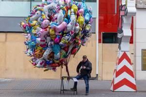 Luftballonverkäufer liest eine Nachricht auf seinem Handy