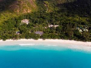 Luftbild der Gästehäuser im Palmenwald an der Bucht Anse Lazio auf Praslin (Seychellen), mit türkisblauem Meer und weißem Sandstrand