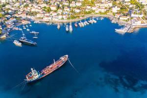 Luftbild der griechischen Insel Spetses im Sommer und einem Handelsschiff vor dem Hafen im blauen ägäischen Meer
