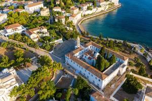 Luftbild der Kirche und des ehemaligen Klosters Agios Nikolaos am Ufer von Spetses, Griechenland