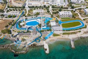 """Luftbild des Wasserparks """"Aqua Paros"""" in Naoussa, Griechenland, mit langen Wasserrutschen, die ins Mittelmeer führen"""