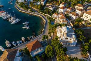 Luftbild einer griechischen Kirche und des malerischen Hafens vor der griechischen Insel Spetses in der Ägäis
