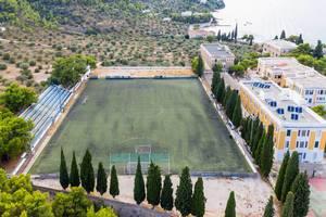 Luftbild eines grünen Fußballfelds mit kleiner Tribüne, am Ligoneri- und Kaikistrand auf der Insel Spetses