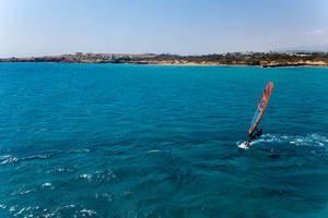 Luftbild eines Mannes auf einem Windsurfbrett auf den Wellen des Meeres vor Paros, Griechenland