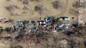 Luftbild eines Schrottplatzes am Waldrand. Ländliche Gegend