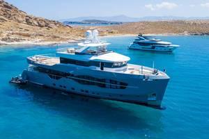 Luftbild und Nahaufnahme einer mehrstöckigen Yacht Q.M., designt von Can Yalman mit Sonnendeck vor der Felsenküste am Strand Tourkou Ammos auf Paros