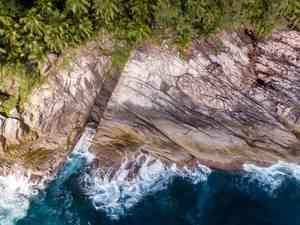 Luftbild von den Wellen des Indischen Ozeans vor den Ros Lepa Klippen auf Mahé, Seychellen