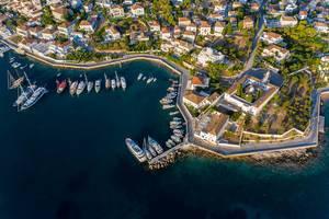 Luftbild von Luxusyachten und Motorbooten an der Küste von Baltiza, Spetses in Griechenland, mit Blick auf die griechische Kirche Agios Nikolaos