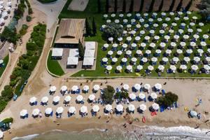 Luftbild von Menschen am Strand Hinitsa nahe Porto Heli, mit aufblasbaren Luftmatratzen und Wasserspielzeug