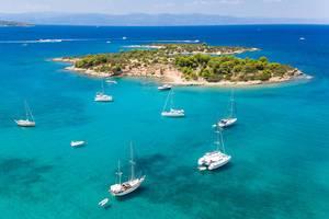 Luftbild von Segelbooten und Katamarane auf dem klaren blauen Wasser vor der unbewohnten griechischen Insel Chenesar